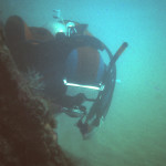 Delray Wreck diver next to boiler sticking out of dand in 1978